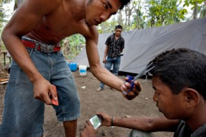 148934889-man-having-his-hair-cut-in-jungle-camp-gettyimages
