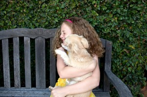 148984029-girl-sitting-with-kissing-dog-gettyimages