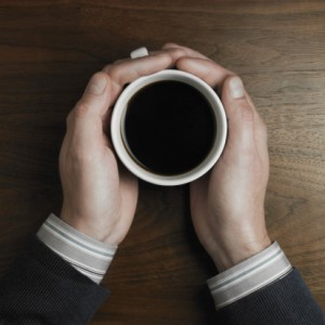 468764761-man-on-desk-holding-cup-of-coffee-close-up-gettyimages